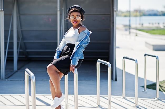 Elegante modello afroamericano in occhiali cappello, giacca di jeans e gonna nera poste all'aperto.