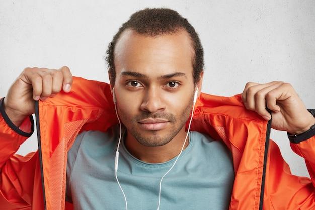 Elegante modello maschile attraente con setole, ascolta la musica utilizza gli auricolari, tiene le mani sulla giacca a vento arancione,