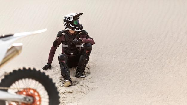 Elegante motociclista con moto nel deserto
