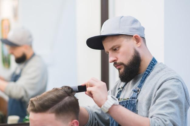 Elegante parrucchiere con barba crea acconciatura maschile con forbice. tagli da uomo in barbiere