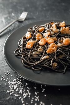Elegante piatto nero di pasta con inchiostro seppia e gamberi accanto al sale marino e forchetta d'argento con sfondo nero con texture