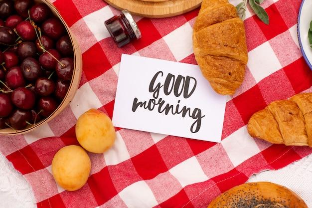 Elegante prato verde da picnic. cornetti freschi e una teiera con tè su un copriletto vicino a un cappello di vimini femmina. contenuto di instagram