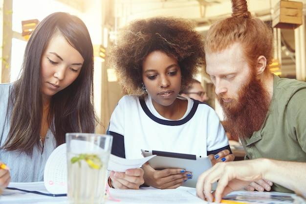 Elegante ragazza africana con anello al naso utilizzando tavoletta digitale insieme al suo collega hipster con folta barba mentre femmina asiatica seria che fa lavoro di ufficio durante la sessione di brainstorming allo spazio di coworking