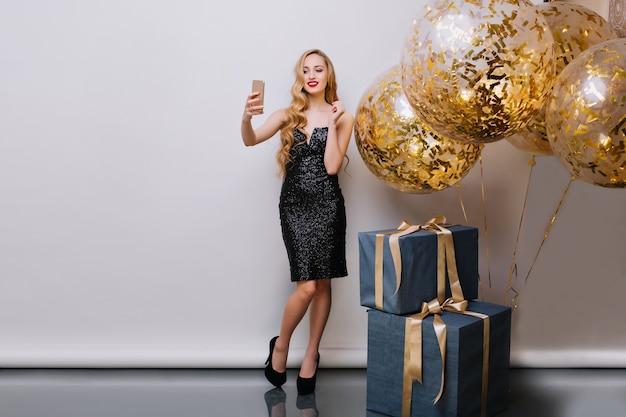 Elegante ragazza bionda con labbra rosse, fare foto prima del compleanno, utilizza lo smartphone. ritratto dell'interno di splendida giovane donna con lunghi capelli biondi in posa vicino a regali e palloncini con sorriso.