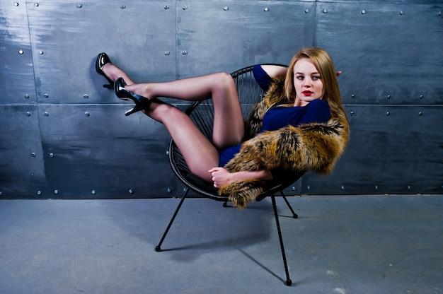 Elegante ragazza bionda usura sulla pelliccia e abito combinato posato sulla sedia contro la parete d'acciaio