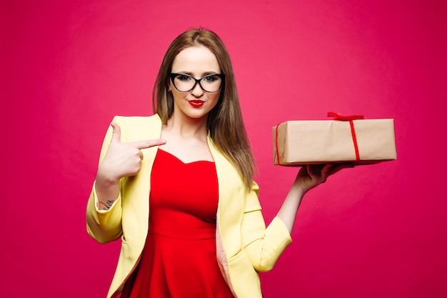 Elegante ragazza in abito rosso, giacca gialla e occhiali cat-eye poi