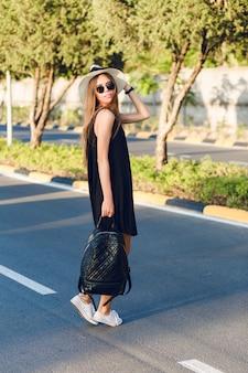 Elegante ragazza in piedi sulla strada che indossa un abito nero corto, cappello di paglia, occhiali neri, scarpe da ginnastica bianche e zaino nero. sorride ai caldi raggi del sole al tramonto