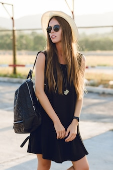 Elegante ragazza in piedi vicino alla strada che indossa un abito nero corto, cappello di paglia, occhiali neri e zaino nero. sorride ai caldi raggi del sole al tramonto