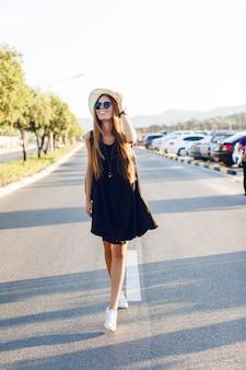 Elegante ragazza in piedi vicino alla strada che indossa un abito nero corto, cappello di paglia, occhiali neri, scarpe da ginnastica bianche e zaino nero. sorride ai caldi raggi del sole al tramonto
