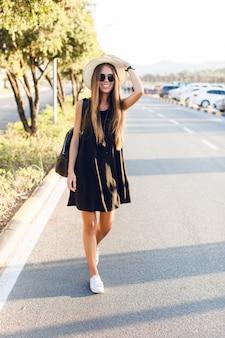 Elegante ragazza in piedi vicino alla strada che indossa un abito nero corto, cappello di paglia, occhiali neri, scarpe da ginnastica bianche e zaino nero. sorride e tiene il suo cappello con la mano