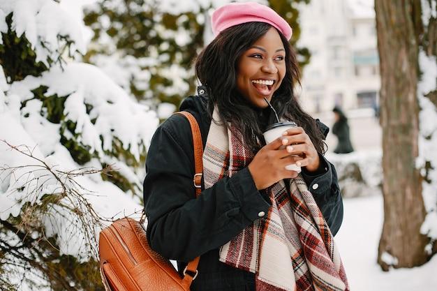 Elegante ragazza nera in una città d'inverno