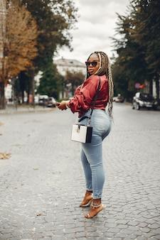 Elegante ragazza nera in una città estiva