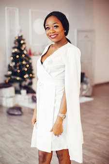 Elegante ragazza nera nella stanza decorata di natale