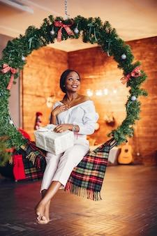 Elegante ragazza nera nelle decorazioni natalizie