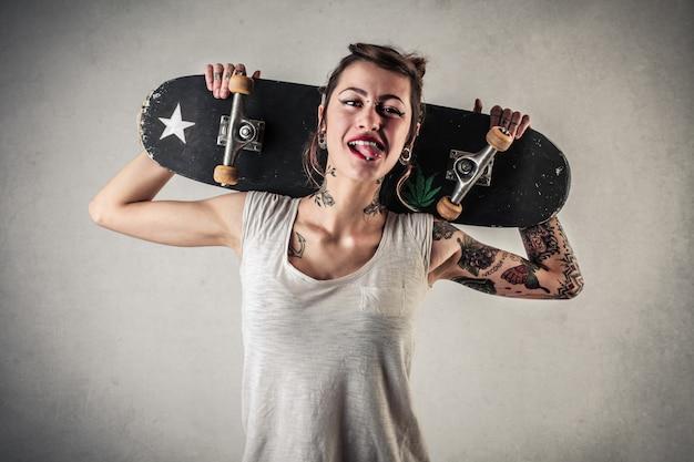 Elegante ragazza tatuata con uno skateboard
