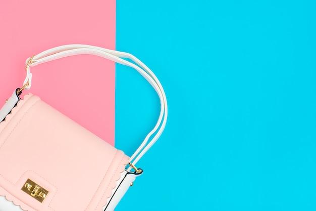 Elegante rosa pastello, borsa bianca su due colori blu, sfondo rosa laici piatti