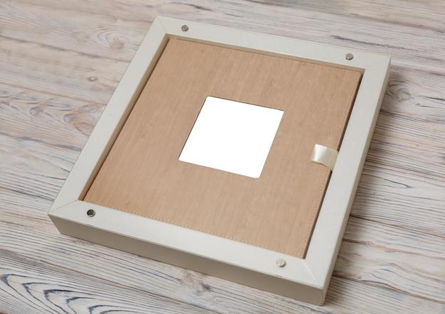 Elegante scatola per album fotografici .. scatola di cartone per un album fotografico di famiglia. scatola con album di foto di nozze con copyspace. fotolibro di matrimonio in pelle nella confezione.