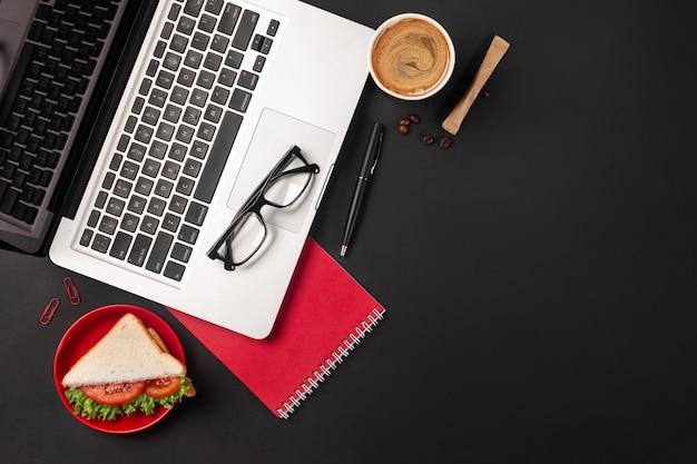 Elegante scrivania da ufficio nera con laptop, tazza di caffè e un panino per il pranzo. vista dall'alto