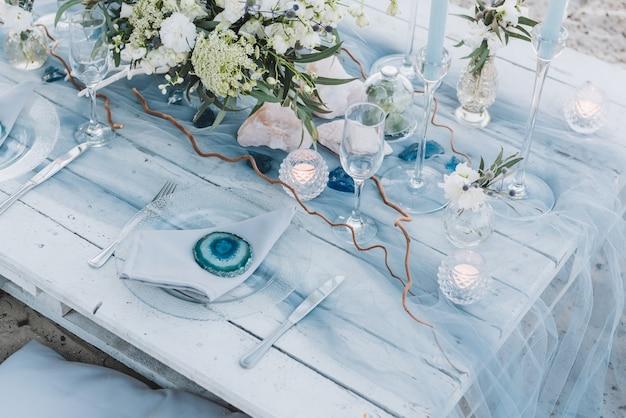 Elegante set da tavola in pastelli blu per un matrimonio in spiaggia