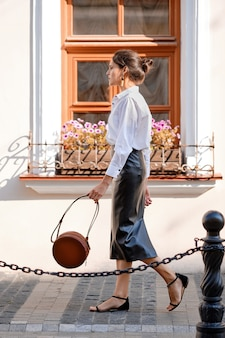 Elegante signora in gonna di pelle e camicia bianca che cammina per strada con borsa a mano in pelle