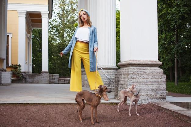 Elegante signora in pantaloni gialli, giacca blu e turbante