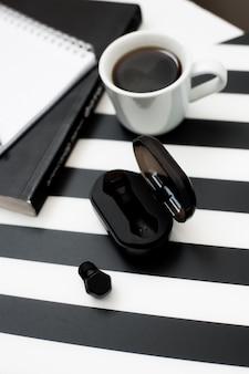 Elegante spazio di lavoro minimalista con finto taccuino, matita, tazza di caffè, auricolare wireless