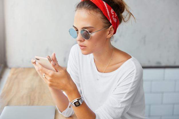 Elegante studentessa indossa occhiali da sole, fascia rossa e maglione bianco, scarica i file sul cellulare, si siede in una caffetteria, ha un'espressione seria. la donna utilizza le moderne tecnologie e internet