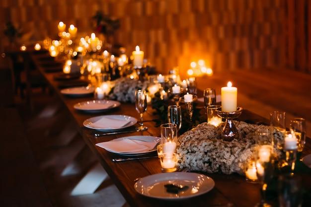 Elegante tavola decorata con fiori e candele del nontiscordardime intorno ai piatti su fondo di legno