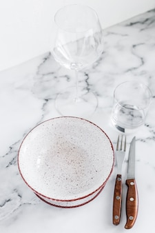 Elegante tavolo elegante impostazione con piatti in ceramica su sfondo di marmo bianco