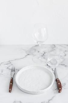 Elegante tavolo elegante impostazione con piatto in ceramica su sfondo di marmo bianco