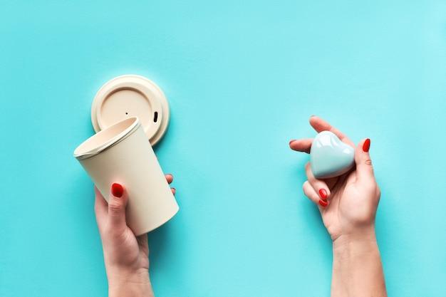 Elegante tazza da viaggio riutilizzabile per caffè eco, tazza in bambù con coperchio e cuore in ceramica in mani femminili. carta menta verde acqua alla moda. tendenza lifestyle eco-sostenibile a zero sprechi.
