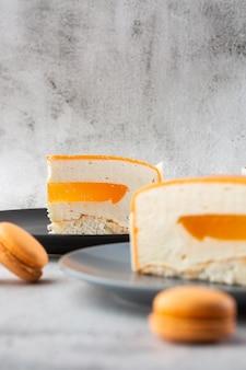 Elegante torta con cocco, frutto della passione, mango e banane, ricoperta di glassa al cioccolato. fetta di torta a strati arancione su fondo di marmo. carta da parati per pasticceria o menu bar. verticale.