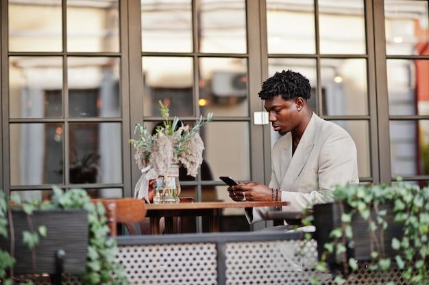 Elegante uomo afro in abito beige vecchia scuola seduto sul caffè con il telefono cellulare. giovane maschio africano alla moda in giacca casual sul torso nudo.