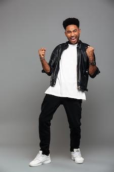 Elegante uomo afroamericano, stringendo i pugni in gesto vincitore, guardando