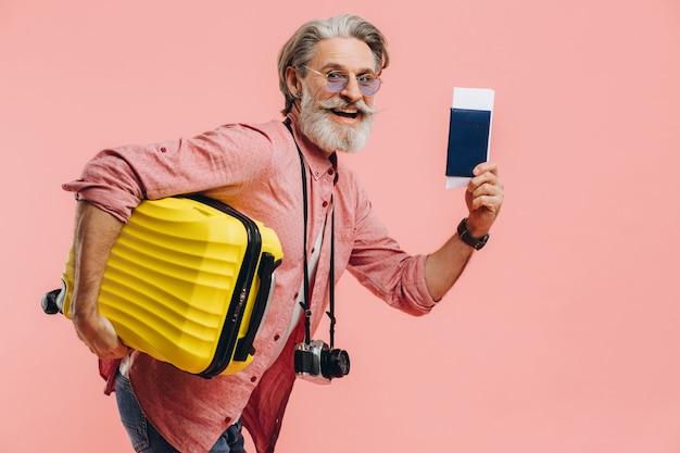 Elegante uomo barbuto con una macchina fotografica tiene una valigia gialla e un passaporto con un biglietto, sorride e si prepara per il viaggio.