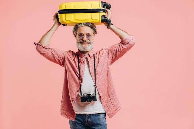 Elegante uomo barbuto con una macchina fotografica tiene una valigia gialla sulla testa