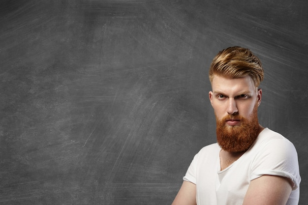 Elegante uomo caucasico con folta barba rossa e taglio di capelli hipster in posa con grave espressione brutale sul viso nell'angolo in basso a destra contro la lavagna vuota con lo spazio della copia per il tuo contenuto