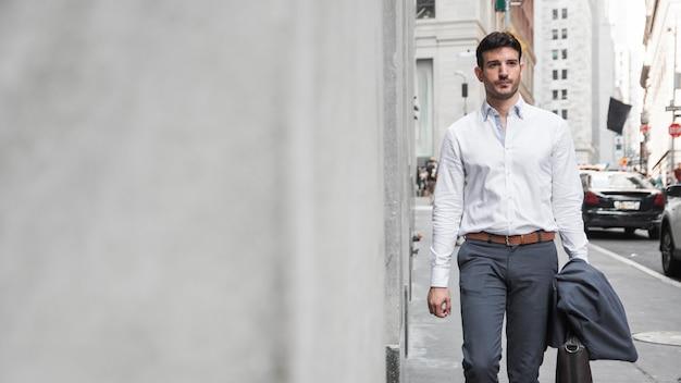 Elegante uomo che cammina sulla strada