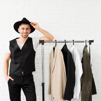 Elegante uomo che indossa un cappello e in piedi accanto al guardaroba