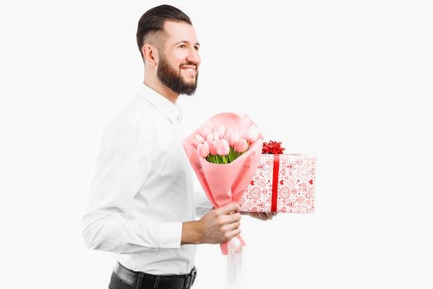 Elegante uomo con la barba con in mano un mazzo di tulipani e una confezione regalo, un regalo per san valentino