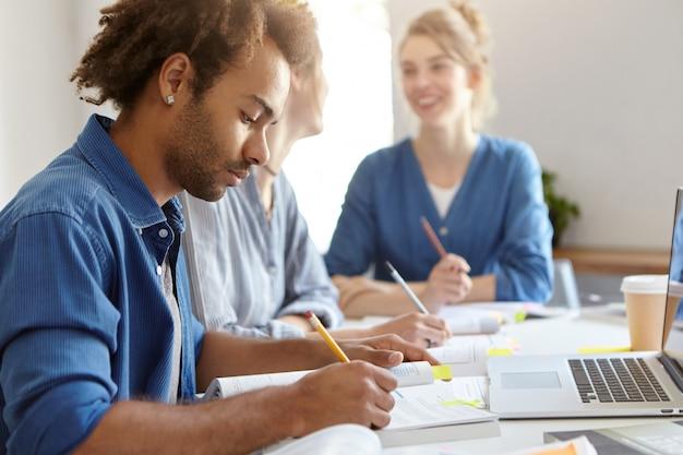 Elegante uomo dalla pelle scura in camicia blu, impegnato con lo studio, seduto vicino ai suoi compagni di gruppo femminili, computer portatile funzionante, scrittura di carta di diploma. gruppo di studenti amichevoli di razze diverse