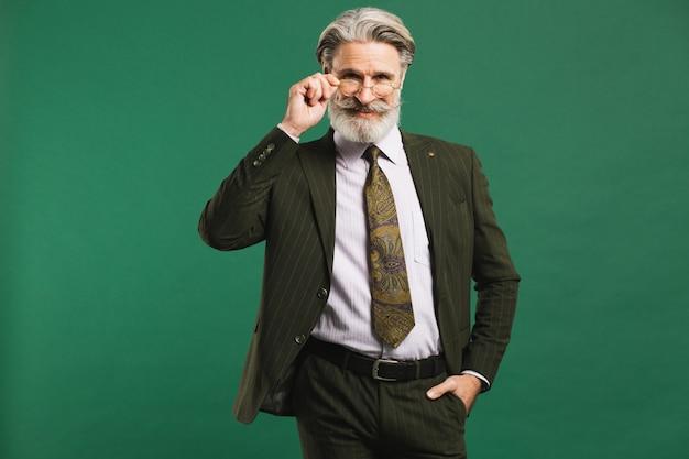 Elegante uomo di mezza età con la barba in tuta tenendo gli occhiali sul muro verde