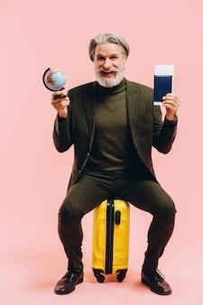 Elegante uomo di mezza età in un vestito si siede sulla valigia gialla e detiene un passaporto e un globo.