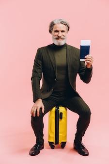 Elegante uomo di mezza età in un vestito si siede sulla valigia gialla e detiene un passaporto.