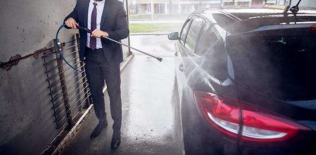 Elegante uomo elegante in un vestito di pulizia lato della macchina con una pistola ad acqua sulla stazione di lavaggio self-service.