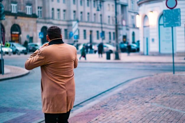 Elegante uomo in giacca marrone, camminando per la strada. vista posteriore