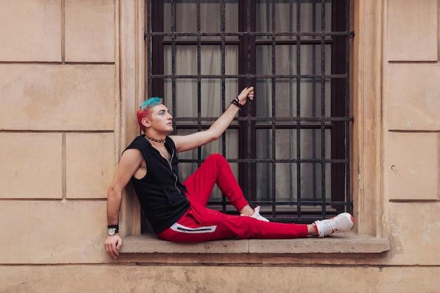 Elegante uomo omosessuale con il trucco, capelli colorati, colletto in pelle con punte in posa sul muro giallo con finestra