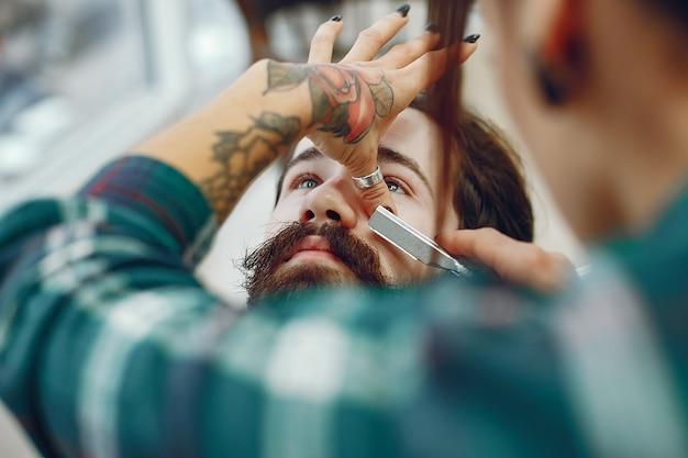 Elegante uomo seduto in un negozio di barbiere