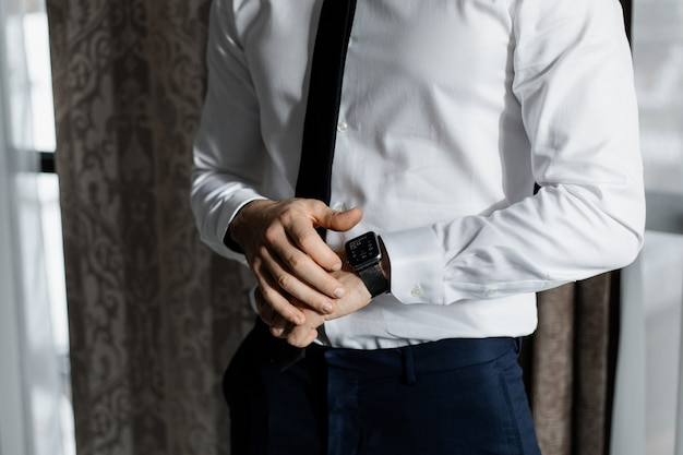 Elegante uomo vestito con una camicia bianca e una cravatta con un orologio intelligente