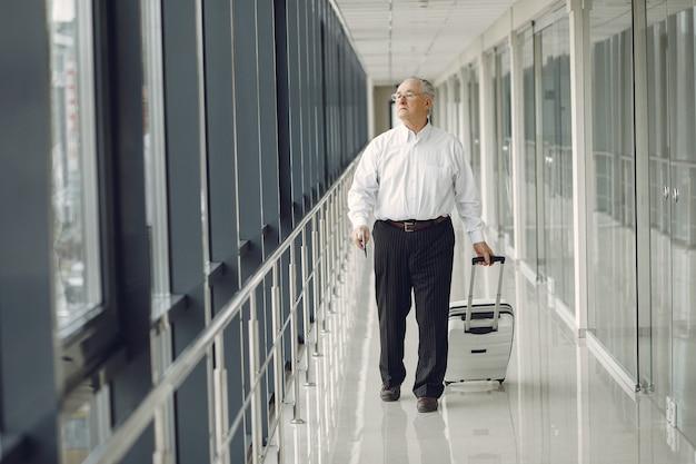 Elegante vecchio all'aeroporto con una valigia